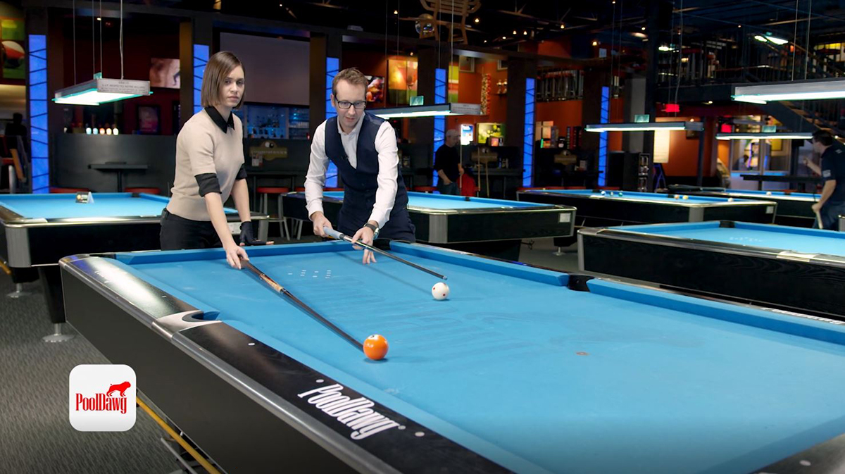 Florian and Valerie use their cues to visualize the line through the five into the pocket, and the parallel line through the cue ball