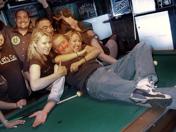 Happy pool team celebrates a great victory with their winning teammate being embraced with hugs and open arms while lying on the pool table.