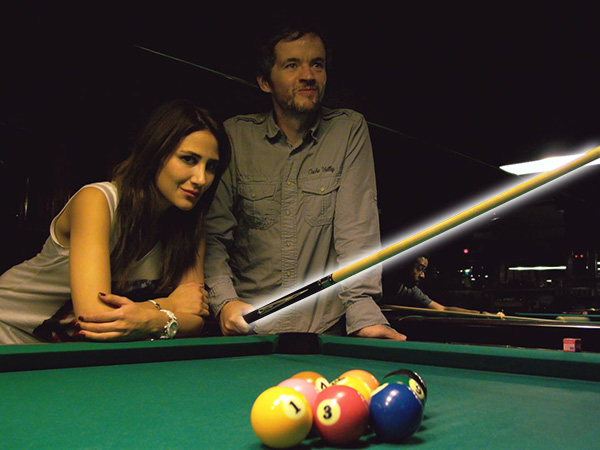 Guy with an attractive woman proudly shows off his pool cue at the pool hall.