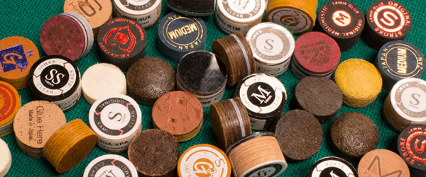 A larger variety of new pool cue tips are laid out on a pool table.