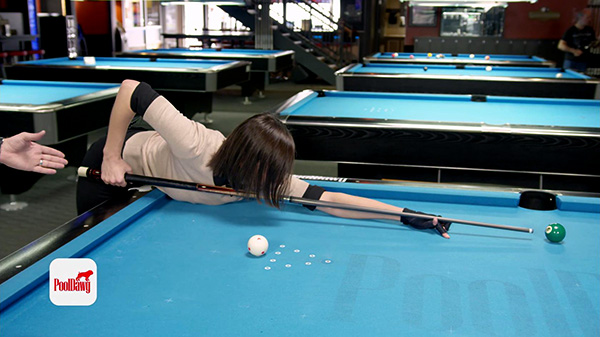 Valerie takes a long shot, with a grip near the end of the cue